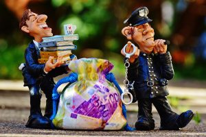 Two figurines. One is a police officer, and the other is a suited man carrying books, with a bag of money in front of him