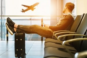 A man on an airport, resting his legs on a small suitcase, looking rather peacefull