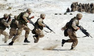 a group of soldiers training in the sand.
