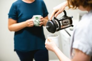 One person made coffee to meet new neighbors, talking to other person and pouring it