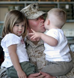 Soldier holding two kids and kissing one of them