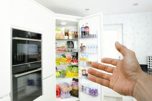 Hand showing the fridge and storing perishable food