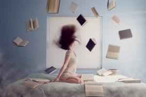 cope with moving stress - girl on a bed with books