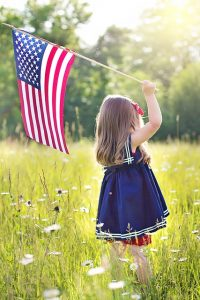 Celebrate July 4th in Columbus, Ohio with your kid on a meadow and a flag