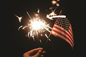 Hand holding a sparkler and a flag