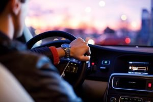 A man driving a car, he has a watch on his left wrist