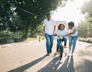 a couple teaching their child to ride a bike