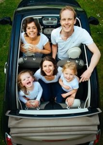 a mother, father and three children sitting inside of the convertible, smiling