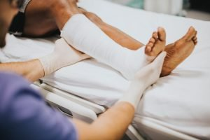Doctor putting bandage on patients leg