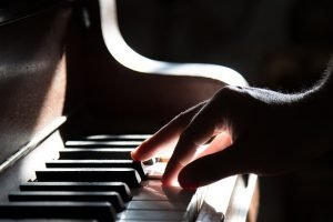 Hand playing the piano before packing musical instruments