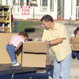 Father and daughter packing boxes