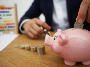 a man putting money in a piggybank