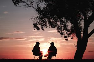 two silhouettes sitting on chair near tree