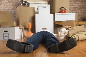 Man lying down on floor with moving boxes