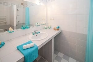 A white bathroom with a blue towel