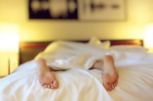 Person's feet in bed sheets