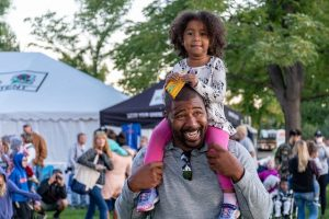 African American Dad holding his daughter on his shoulders in the best place in Ohio to raise children