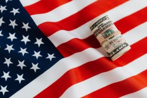 american flag with a roll of money