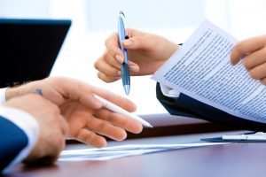 Two people going over some documents and contracts