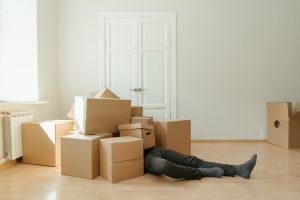 Man lying under boxes.