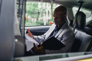 person sitting in a car going through papers