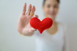 woman showing a small, red, toy heart