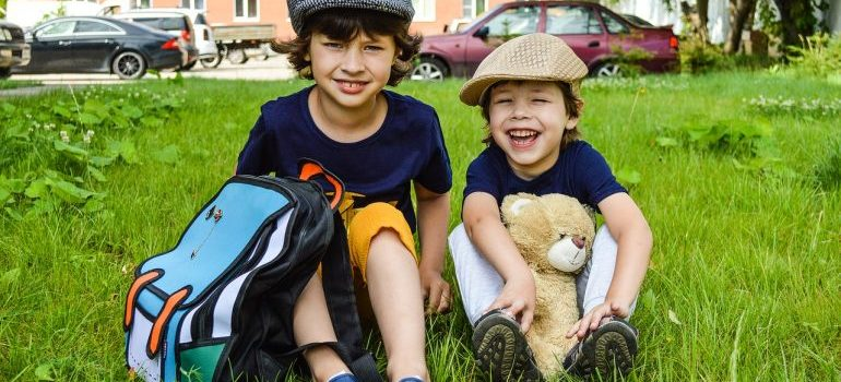 two boys sitting on grass with a backpack and a teddy bear