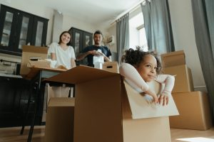 family packing for a move, little girl in a cardboard box playing