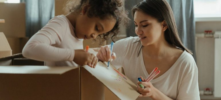 a mother drawing something on a cardboard box with her daughter