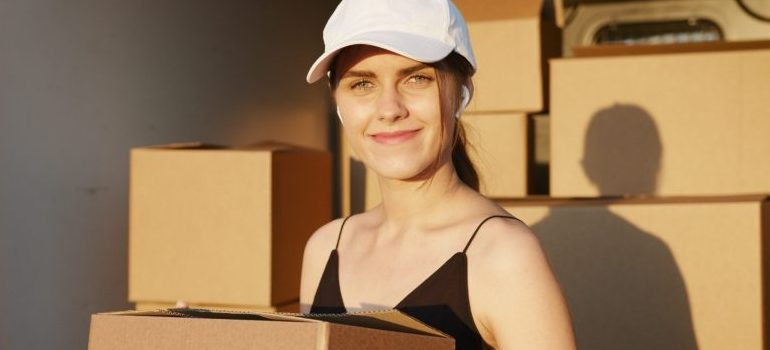 female with a white hat smiling, carrying a moving box