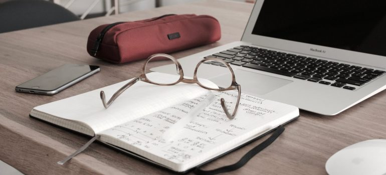 glasses, notebook and a laptop on the table as a way to calculate expenses when you decide between renting and buying
