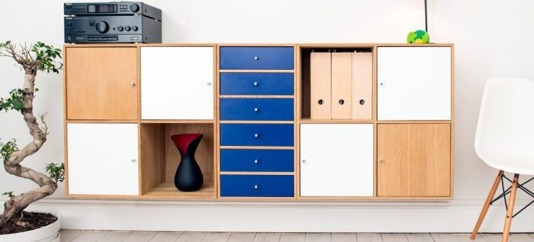wooden piece of furniture with shelves and drawers on the wall