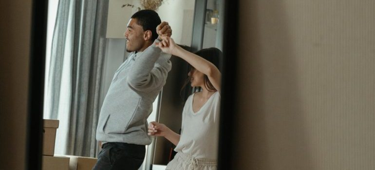 a man and woman dancing in front of the mirror