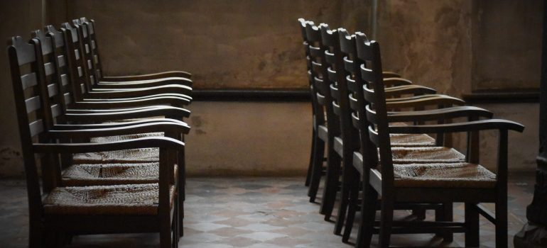 a dozen wooden chairs in a row as items that require climate controlled storage