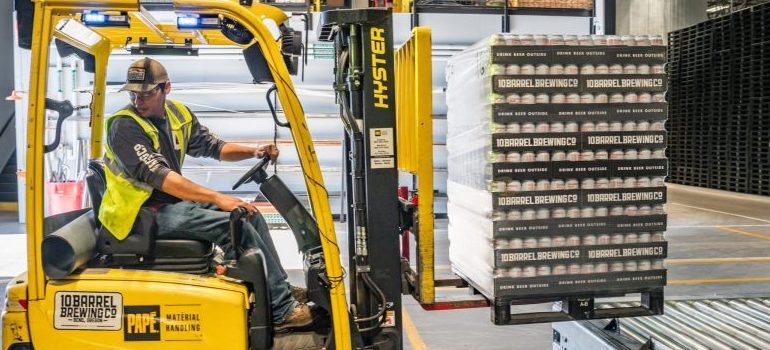 man using a forklift to reorganize a storage unit