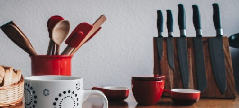 kitchen table with knives, spoons, and mugs