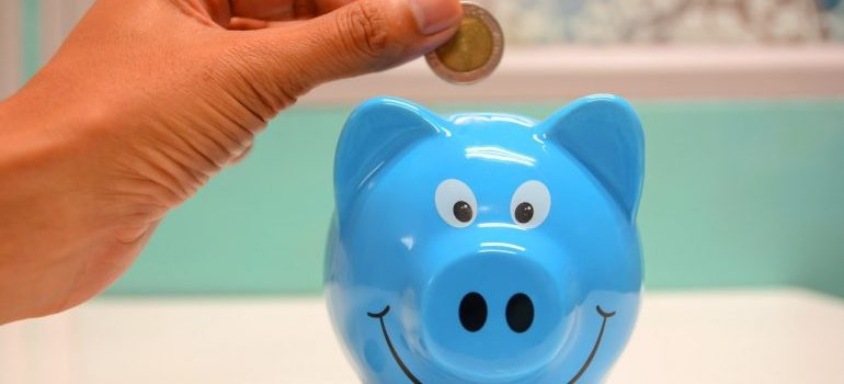 someone holding a coin over a blue pig
