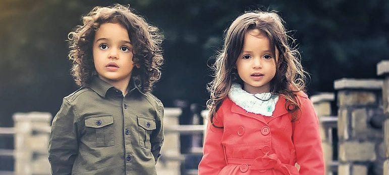 Two kids standing on a bridge