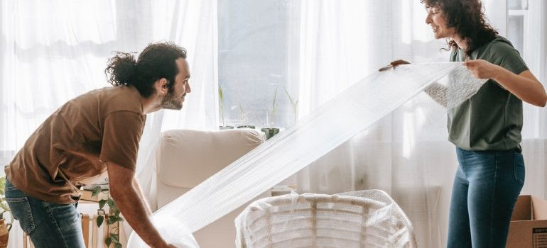 a man and woman wrapping a chair with a bubble wrap