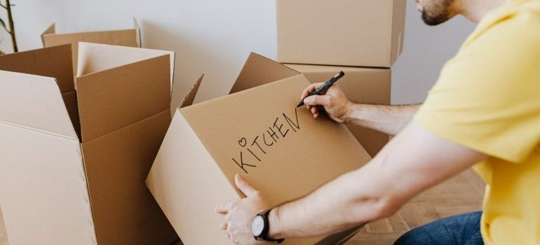 """a man writing the word """"kitchen"""" on a box as one of the moving day rules"""