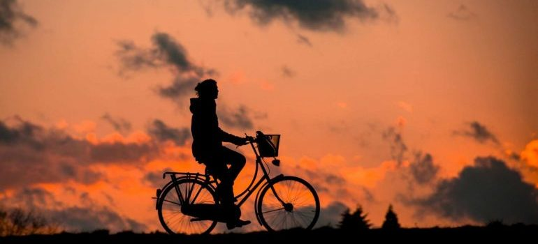 Silhouette of a female person riding a bike while sunset with clouds in the background.
