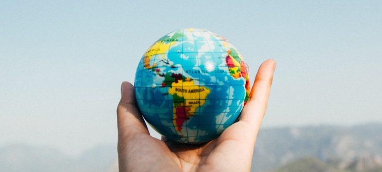 A person holding a miniature globe