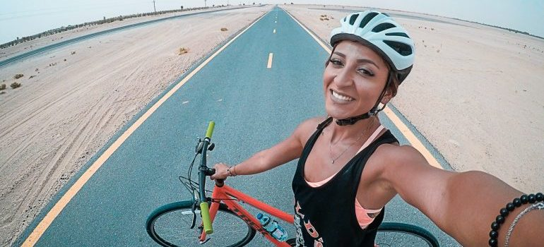 A woman in the middle of the road with a helmet on her head holding a bicycle with a hand and taking a picture with another.