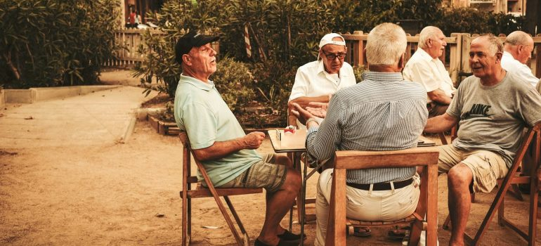 Older men sit around the tables and talk, with bushes and houses in the background.