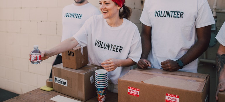 A woman is holding a cup while doing charity work.