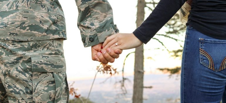 A man in the uniform and woman in civilian clothes holding hands and watching the valley from the hill.