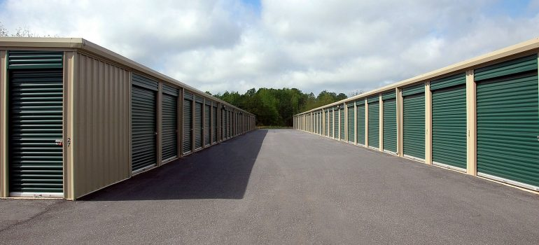 The self-storage units with green doors and concrete passage between two rows of units.