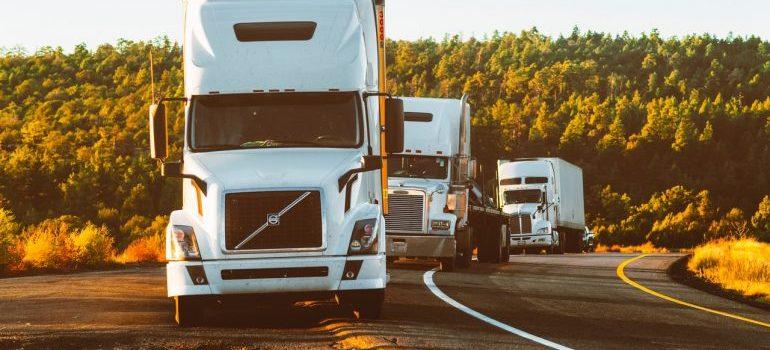 three white trucks on the road
