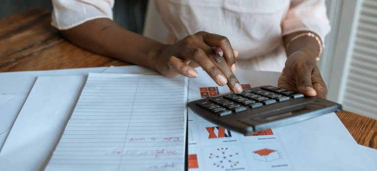 A person is sitting at the table covered with papers and using calculator.