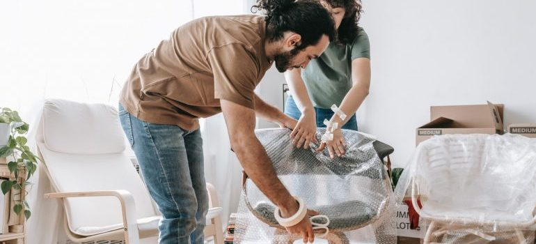 a couple wrapping the furniture using bubble wrap